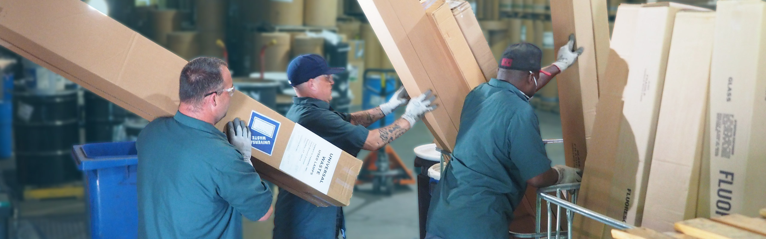 A picture of three NLR workers unloading boxes of spent fluorescent lamps in our UWH warehouse. NLR recycles fluorescent lamps and other universal waste.