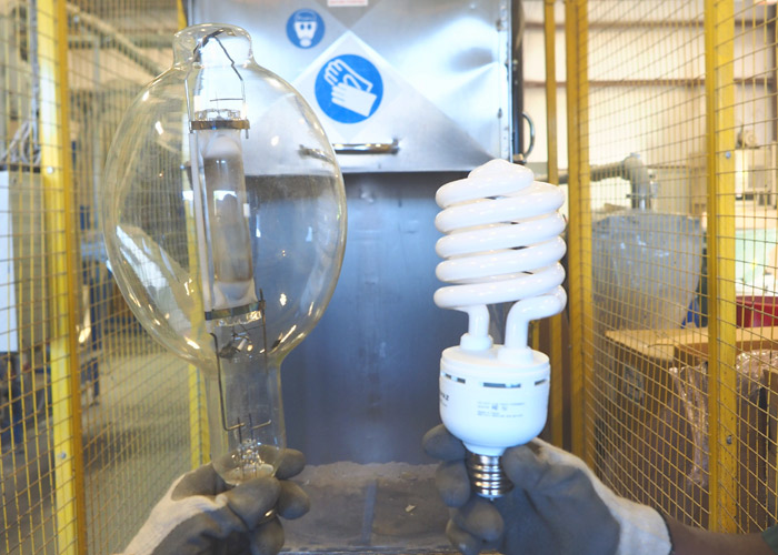 A picture of a large CFL bulb and HID bulb being held up in front of the lamp recycling system. NLR recycles fluorescent lamps and bulbs and other universal waste.