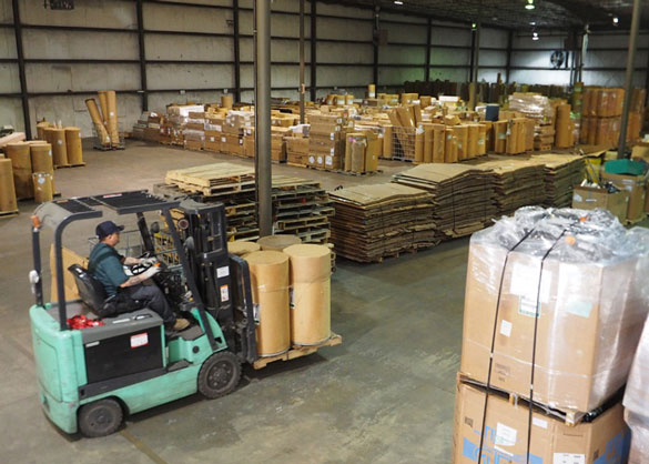 A picture of one of NLR's universal waste handlers driving a forklift in the warehouse. This is where NLR recieves and sorts lamp recycling, electronics recycling, battery recycling, and mercury devices.