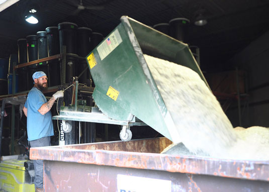 A picture of one of the lamp processing team using a machine to dump the cleaned glass cullet from recycling lamps into a container.