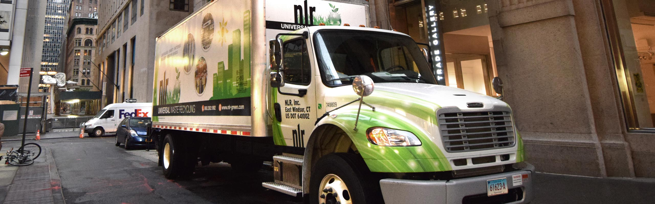 Picture of NLR's green and white box truck at a recycling pick-up in New York City. NLR has a complete fleet of trucks to service our recycling customers.