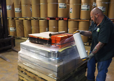 A picture of a universal waste handler wrapping stacked lead acid batteries on a pallet with plastic. NLR follows best practices for the safe shipment and storage of batteries.