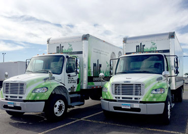 A picture of two of NLR's box trucks used to transport universal waste in and around the city.