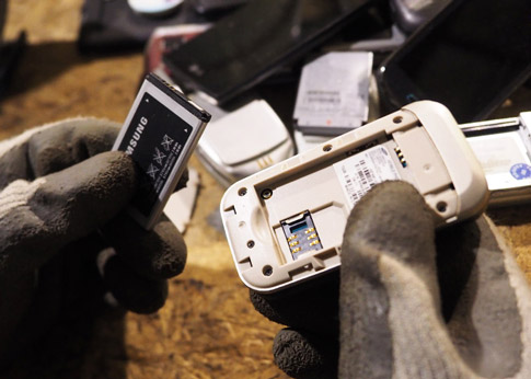 A picture of a lithium ion battery being removed from an old cellphone. NLR recycles lithium ion battery and other battery types.